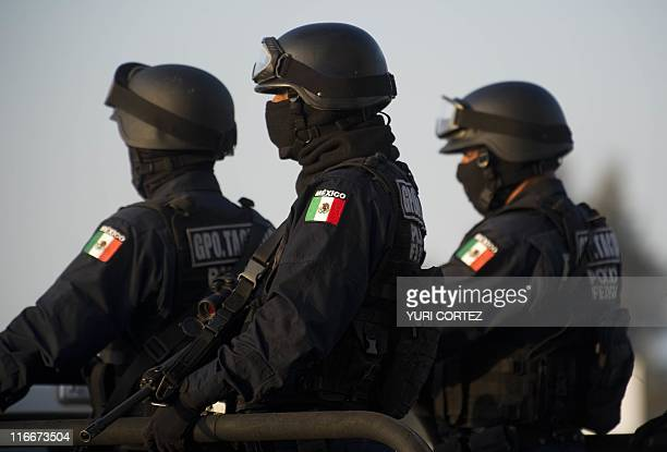 "Federal policemen escort the armoured car carring the member of Los Zetas drug cartel Edgar Huerta Montiel, aka ""El Wache"", before his presentation..."