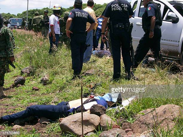 Federal policemen stand next to one of the victims after a Mexican Navy Vice Admiral convoy was attacked by an unidentified armed goup in Churintzio...
