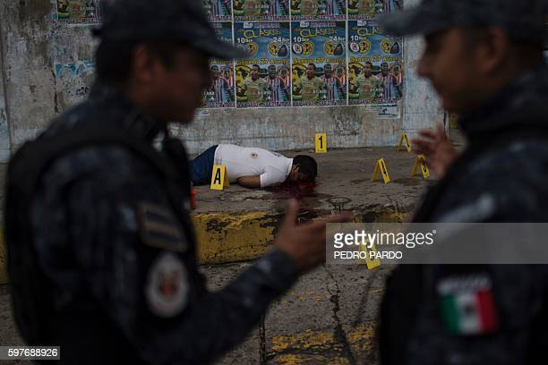Federal policemen talk next to the corpse of a murdered man in Acapulco Guerrero state Mexico on August 29 2016 Acapulco once known as a celebrities...