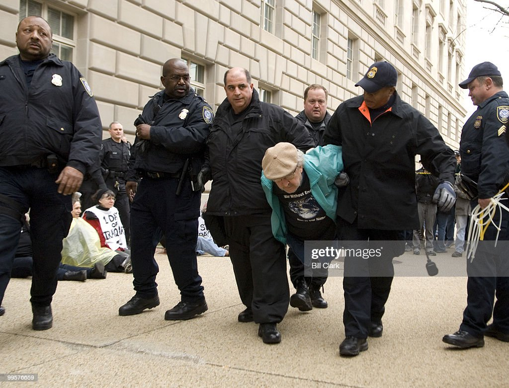 A Federal Protection Service officers arrest Iraq War protesters blocking entrances to the the Internal Revenue Service building on Wednesday morning, March, 19, 2008, the fifth anniversary of the start of the war.