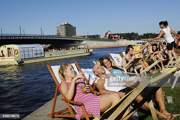 Federal Republic of Germany Berlin Mitte people relaxing with cool drinks in the beach bar 'Capital Beach' at Spree river government district