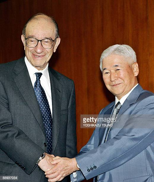 Federal Reserve Board chairman Alan Greenspan shakes hands with his Japanese counterpart Toshihiko Fukui for their talks at the Bank of Japan...