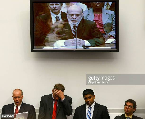 Federal Reserve Board Chairman Ben Bernanke appears on a television above the heads of Congressional staffers while he testifies before the House...