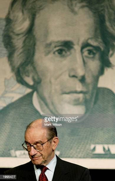 S Federal Reserve Chairman Alan Greenspan stands beneath portrait of Andrew Jackson on an enlargement of the new $20 bill after it was unveiled at...