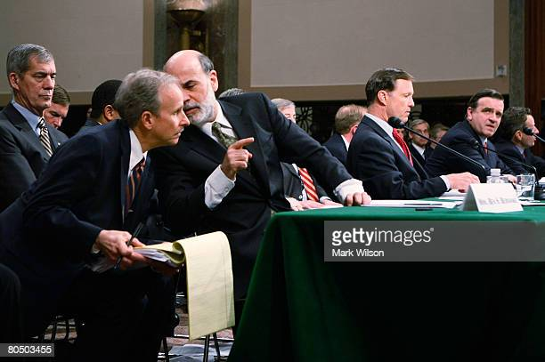 Federal Reserve Chairman Ben Bernanke talks with an associate while testifying as SEC Chairman Christopher Cox Under Secretary of Treasury for...
