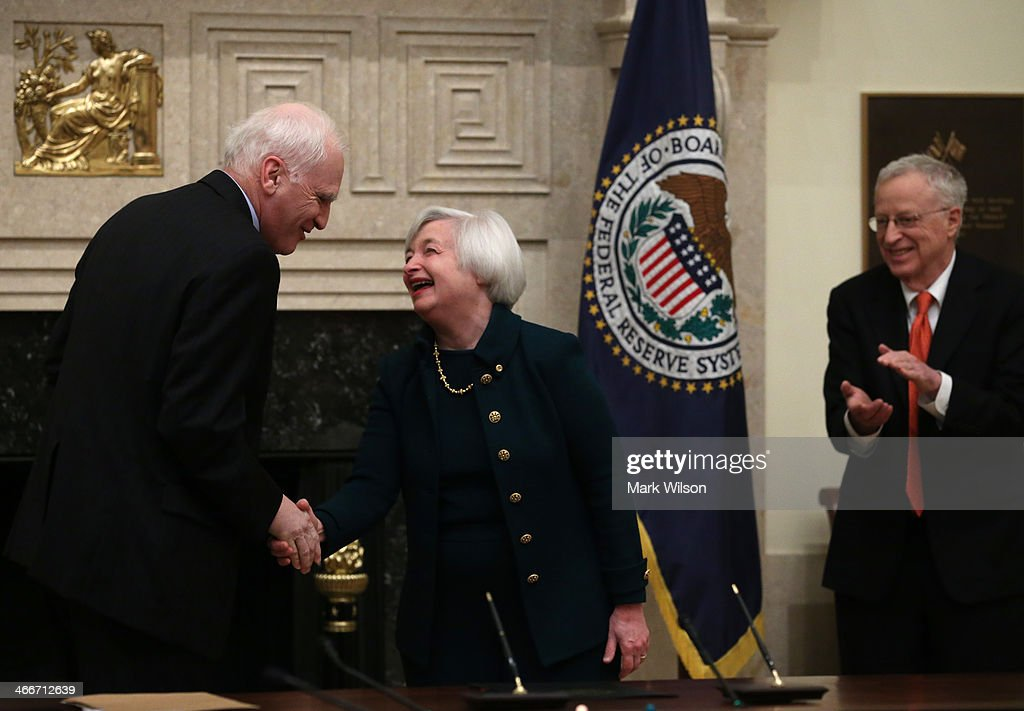 Federal Reserve Vice Chairman Janet Yellen (C) shakes hands with Federal Reserve Board Governor Daniel Tarullo after she was sworn in as Federal Reserve Chairman as her husband George Akerlof (R) stands nearby at the Federal Reserve Building on February 3, 2013 in Washington, DC. Chairman Yellen is replacing Ben Bernanke as Federal Reserve Chairman.