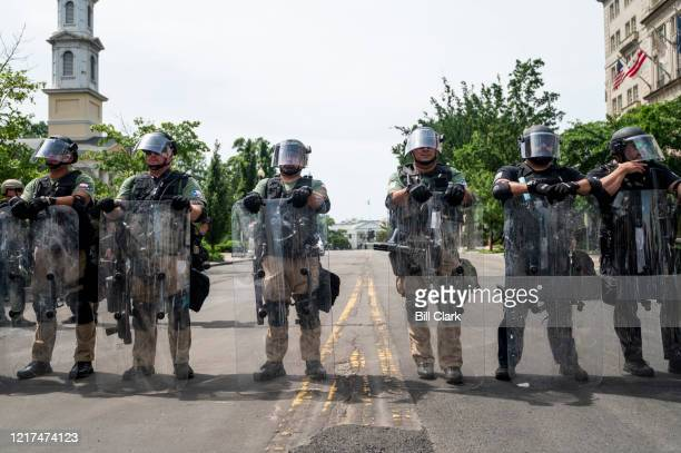 Federal security forces in riot gear block 16th Street at I Street in front of the White House as the George Floyd and police brutality protests...