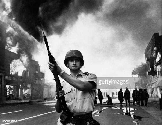 A federal soldier stands guard in a Detroit street on July 25 1967 as buildings are burning during riots that erupted in Detroit following a police...