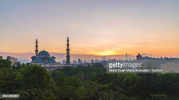Federal Territory Mosque By Trees Against Sky During Sunset