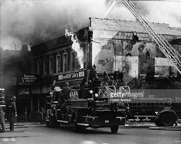 Federal troops ride on a fire engine to protect the firefighters from snipers during the riots in Detroit Michigan July 27 1967