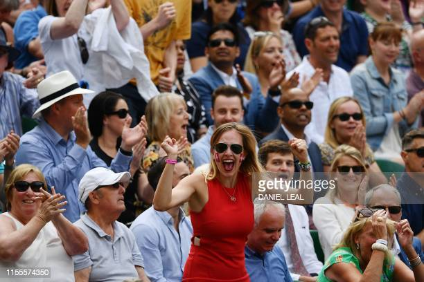 A Federer fan celebrates as Switzerland's Roger Federer breaks the serve of Serbia's Novak Djokovic in the fifth set during the men's singles final...