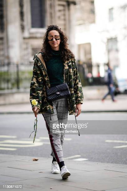 Federica Caiazzo wears sunglasses a green turtleneck wool top a Chanel bag a military camouflage print jacket gray checked pants white sneakers holds...