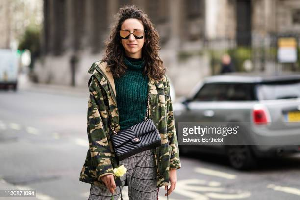 Federica Caiazzo wears sunglasses a green turtleneck wool top a Chanel bag a military camouflage print jacket gray checked pants holds a yellow...
