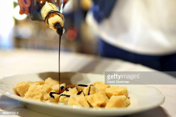Federica Gibellini pours balsamic vinegar over parmesan cheese during a tasting of aged vinegars at Acetaia Leonardi on March 27 2017 in the village...