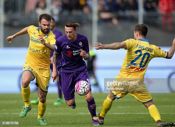 Federico Bernardeschi of ACF Fiorentina competes for the ball with Paolo Sammarco and Daniel Pavlovic of Frosinone Calcio during the Serie A match...