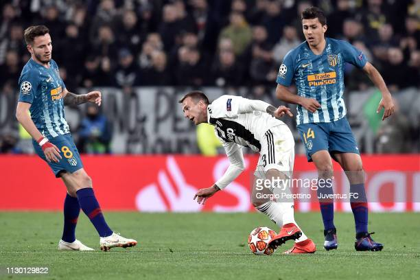 Federico Bernardeschi of Juventus competes for the ball with Saul Niguez and Rodrigo of Club de Atletico Madrid during the UEFA Champions League...