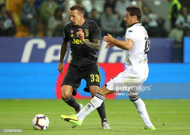 Federico Bernardeschi of Juventus is challenged by Massimo Gobbi of Parma Calcio during the serie A match between Parma Calcio and Juventus at Stadio...