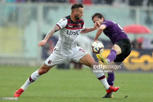 Federico Chiesa of ACF Fiorentina battles for the ball with Mitchell Dijks of Bologna FC during the Serie A match between ACF Fiorentina and Bologna...