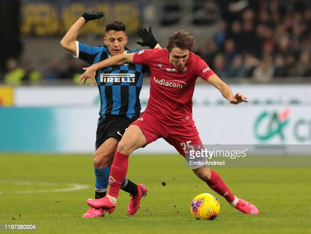 Federico Chiesa of ACF Fiorentina is challenged by Alexis Sanchez of FC Internazionale during the Coppa Italia Quarter Final match between FC...