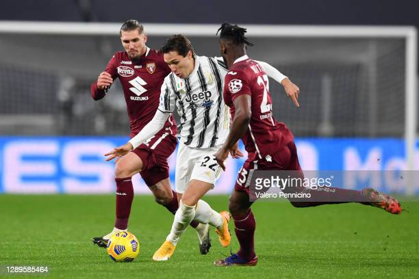 Federico Chiesa of Juventus is challenged by Vojnovic Lyanco of Torino FC and Soualiho Meite of Torino FC during the Serie A match between Juventus...