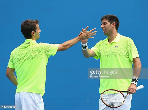 Federico Delbonis of Argentina and Albert Ramos of Spain talk tactics in their first round doubles match against Lukasz Kubot of Poland and Robert...