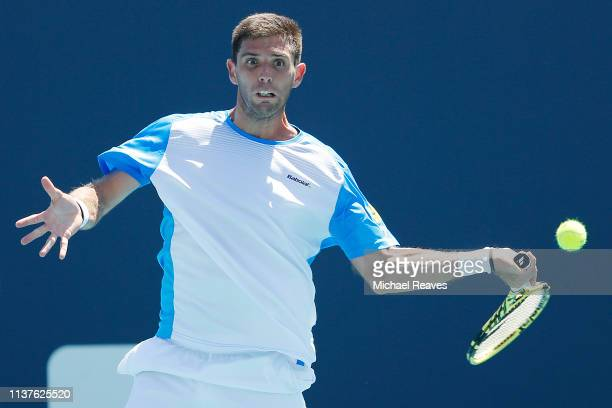 Federico Delbonis of Argentina returns a shot to John Millman of Australia during Day 5 of the Miami Open Presented by Itau at Hard Rock Stadium on...