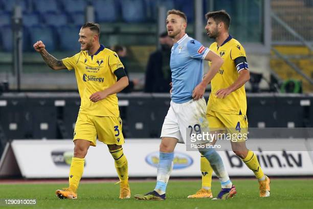 Federico Dimarco and Miguel Veloso of Hellas Verona F.C. Celebrate after Manuel Lazzari of SS Lazio scored an own goal to make it the first goal for...