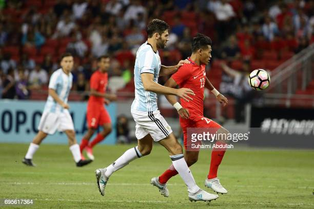 Federico Fazio of Argentina and Khairul Nizam of Singapore chase for the ball during the International Test match between Argentina and Singapore at...