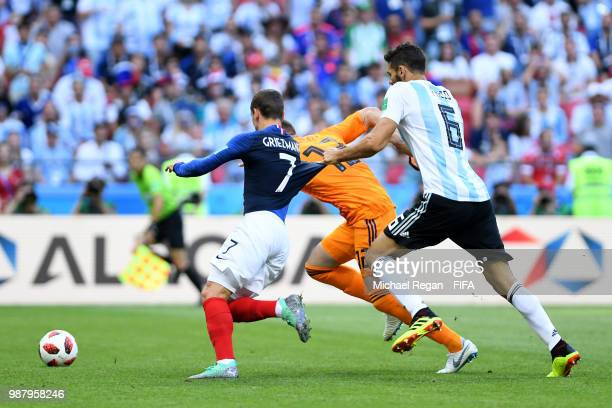 Federico Fazio of Argentina grabs Antoine Griezmann of France's shirt as they battle for the ball alongside Franco Armani of Argentina during the...
