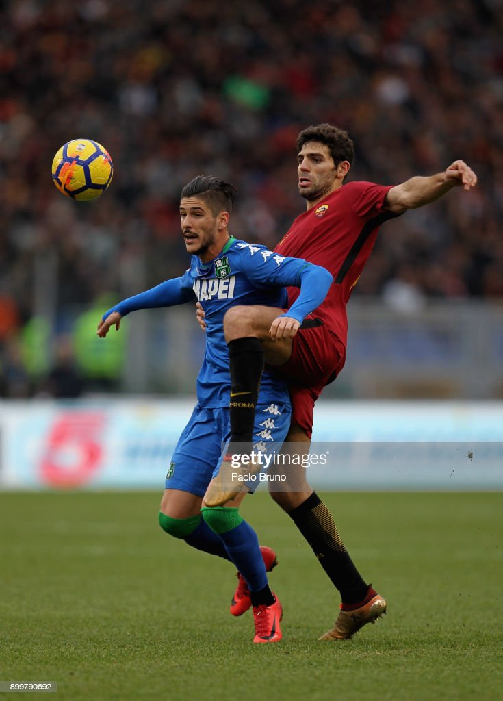 Federico Fazio of AS Roma competes for the ball with Diego Falcinelli of US Sassuolo during the serie A match between AS Roma and US Sassuolo at Stadio Olimpico on December 30, 2017 in Rome, Italy.