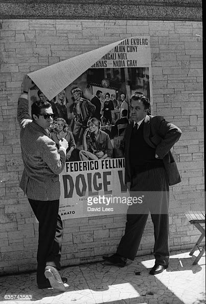 Federico Fellini holds up a poster for his film 'La Dolce Vita' with Marcello Mastroianni ca 1960
