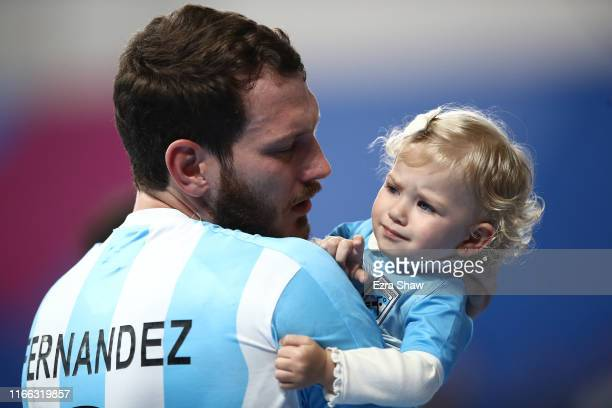 Federico Fernandez carries his daughter Emilia Fernandez during celebrations after the victory of Argentina over Chile in Men`s Handball Gold Medal...