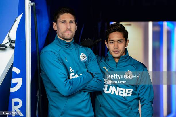 Federico Fernandez of Newcastle United and Yoshinori Muto wait to run outside to warm up during the Premier League match between Leicester City and...