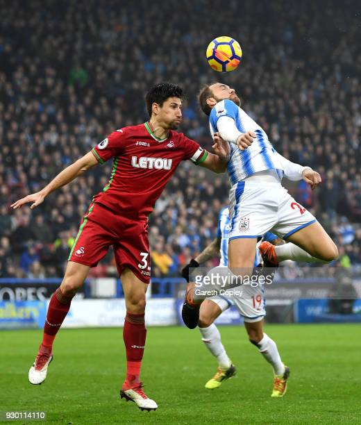 Federico Fernandez of Swansea City and Laurent Depoitre of Huddersfield Town battle for the header during the Premier League match between...