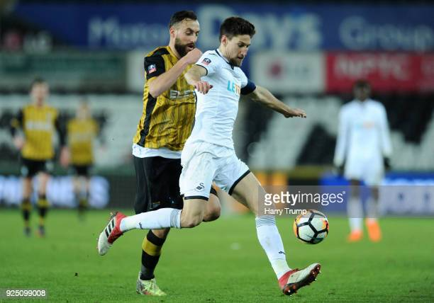 Federico Fernandez of Swansea City gets to the ball ahead of Atdhe Nuhiu of Sheffield Wednesday during the Emirates FA Cup Fifth Round Replay match...