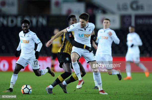 Federico Fernandez of Swansea City is tackled by Lucas Joao of Sheffield Wednesday during the Emirates FA Cup Fifth Round Replay match between...