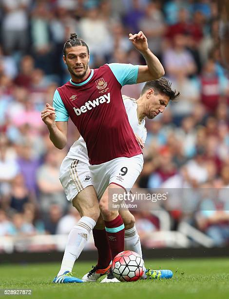 Federico Fernandez of Swansea City tries to tackle Andy Carroll of West Ham during the Barclays Premier League match between West Ham United and...
