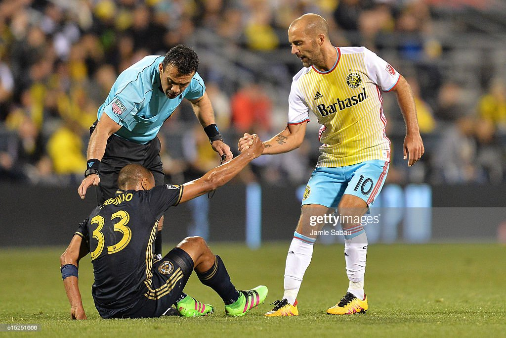 Federico Higuain #10 of the Columbus Crew SC helps up Fabinho #33 of the Philadelphia Union in the second half as referee Hilario Grajeda checks on Fabinho on March 12, 2016 at MAPFRE Stadium in Columbus, Ohio. Philadelphia defeated Columbus 2-1.