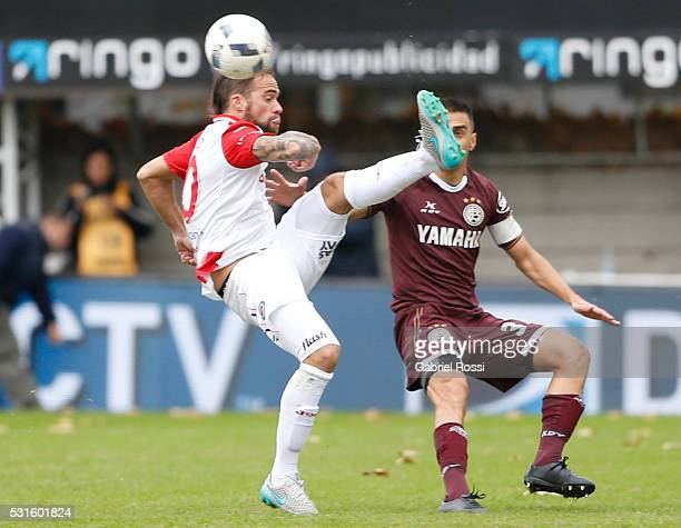 Federico Insua of Argentinos Juniors fights for the ball with Maximiliano Vela‡zquez of Lanus during a match between Argentinos Juniors and Lanus as...