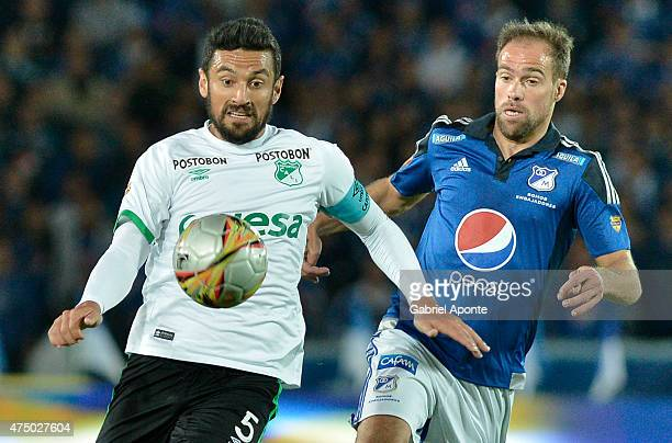 Federico Insua of Millonarios struggles for the ball with Andres Perez of Deportivo Cali during a first leg match between Millonarios and Deportivo...