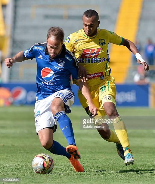 Federico Insua of Millonarios struggles for the ball with Felipe Alarcon of Atletico Huila during a match between Millonarios and Ateltico Huila as...