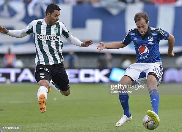 Federico Insua of Millonarios struggles for the ball with Francisco Najera of Atletico Nacional during a match between Millonarios and Atletico...