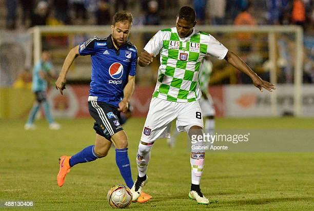 Federico Insua of Millonarios struggles for the ball with Francisco Rodriguez of Boyaca Chico during a match between Boyaca Chico and Millonarios as...