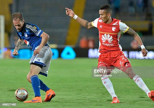 Federico Insua of Millonarios struggles for the ball with Francisco Mesa of Santa Fe during a match between Millonarios and Independiente Santa Fe as...