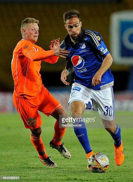 Federico Insua of Millonarios struggles for the ball with George Saunders of Envigado during a match between Millonarios and Envigado FC as part of...