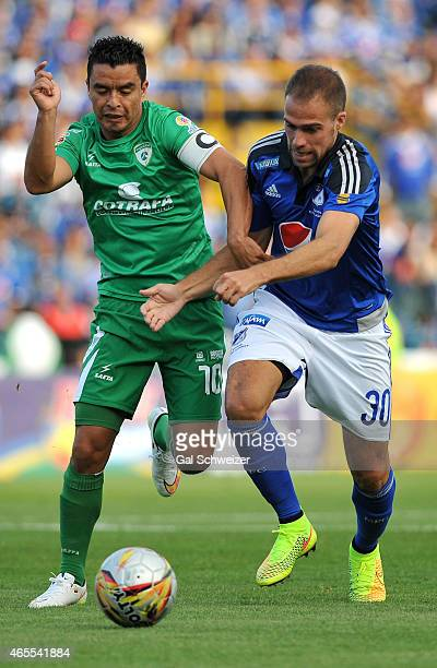 Federico Insua of Millonarios struggles for the ball with Stalin Motta of La Equidad during a match between Millonarios and La Equidad as part of...