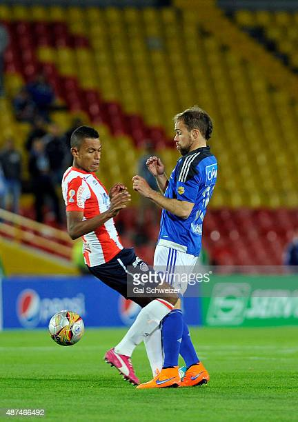 Federico Insua of Millonarios struggles for the ball with William Tesillo of Junior during a match between Millonarios and Junior as part of Liga...