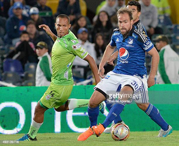 Federico Insua of Millonarios struggles for the ball with Yonaider Ortega of Jaguares FC during a match between Millonarios and Jaguares FC as part...