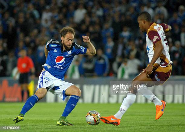 Federico Insua of Millonarios vies for the ball with Davinson Monsalve of Deportes Tolima during a match between Millonarios and Deportes Tolima as...