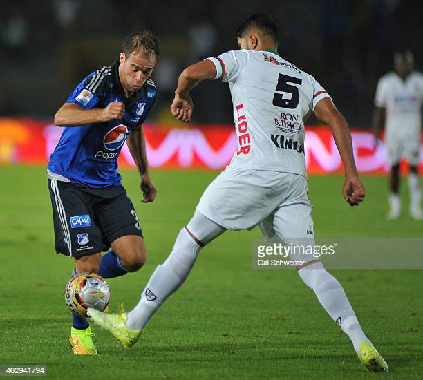 Federico Insua of Millonarios vies for the ball with Larry Vasquez Patriotas during a match between Millonarios and Patriotas FC as part of second...